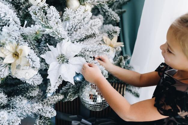 青とグレーのスタイルのクリスマスツリーに飾りを置く白人少女の手のクローズアップ Premium写真