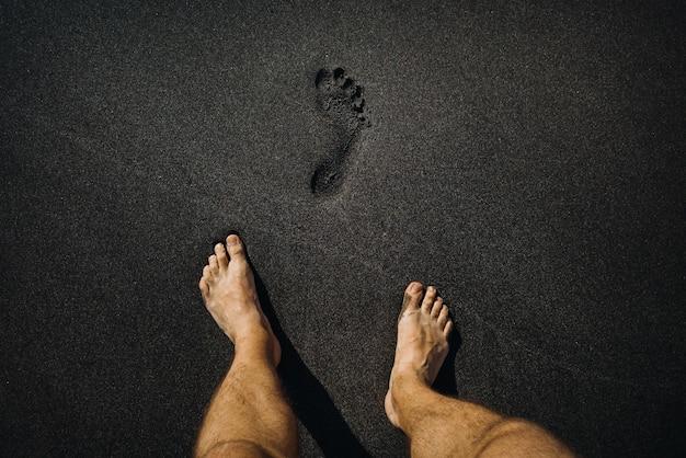 ビーチの火山の黒い砂の上を歩いている男性の足跡と足のクローズアップ。 Premium写真