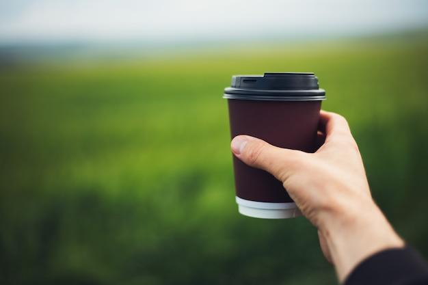 흐린 된 녹색 잔디의 배경에 일회용 종이 커피 컵을 들고 남성 손 클로즈업. 프리미엄 사진