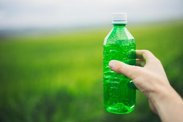 녹색 플라스틱 병을 들고 남성 손 클로즈업 야외 배경을 흐리게에 물을 뿌려. 프리미엄 사진