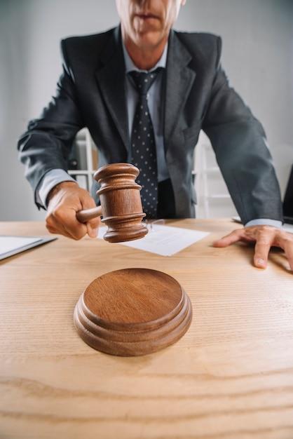 Крупный план судьи-мужчины, который дает вердикт, ударяя молотком на стол Бесплатные Фотографии