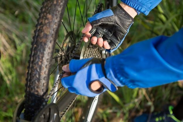Крупным планом мужской горный байкер, исправление его велосипедной цепи Premium Фотографии