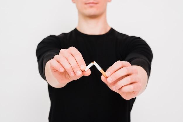 Крупный план мужской руки, ломающей сигарету Бесплатные Фотографии