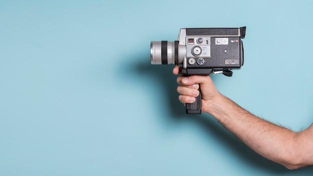 青い背景に昔ながらのビデオカメラを持っている人間の手のクローズアップ Premium写真