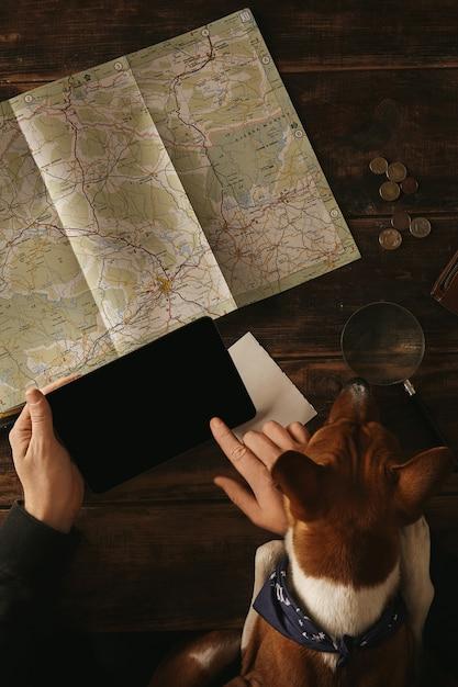 호기심이 많은 Basenji 개가 탁상에 발로 보이는 동안 도로지도가있는 오래된 나무 테이블에 모험 경로를 계획하면서 태블릿을 들고 손가락으로 슬라이드하는 사람의 손을 닫습니다. 무료 사진