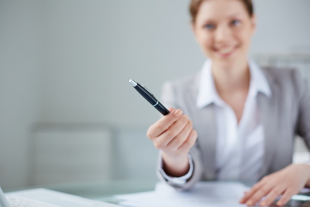 Close-up of manager holding a pen with blurred background Free Photo