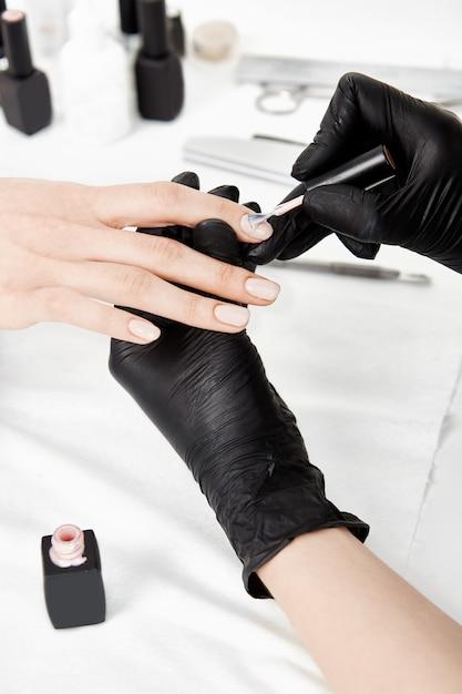 ジェルポリッシュを適用する手袋でネイリストの手のクローズアップ。 無料写真