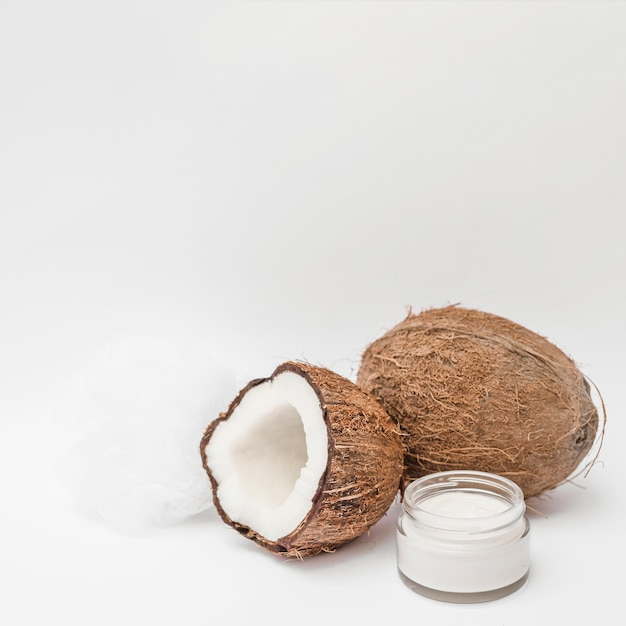Close-up of moisturizing cream; loofah and coconut on white backdrop Free Photo