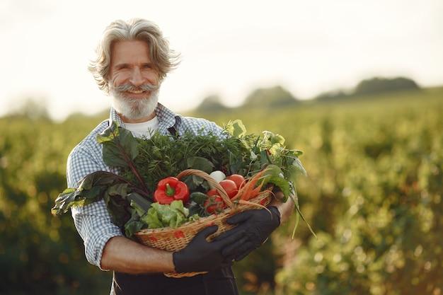 野菜のバスケットを持って古い農家のクローズアップ。その男は庭に立っています。黒いエプロンのシニア。 無料写真