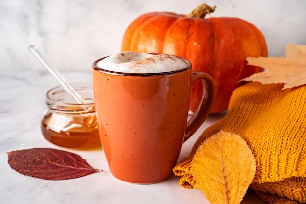 白い表面にコーヒーやカボチャのスパイスラテ、紅葉、カボチャ、蜂蜜の瓶とオレンジ色のカップのクローズアップ Premium写真