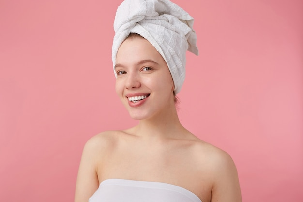 彼女の頭にタオルを持ってスパの後のポジティブな若い素敵な女性のクローズアップ、広く笑顔、幸せで陽気に見える、立っています。 無料写真