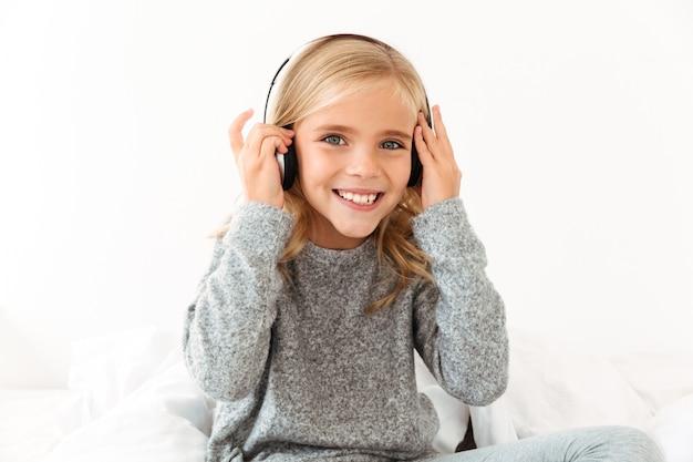 音楽を聴きながら彼女のヘッドフォンに触れるかなり笑顔の少女のクローズアップ、 無料写真