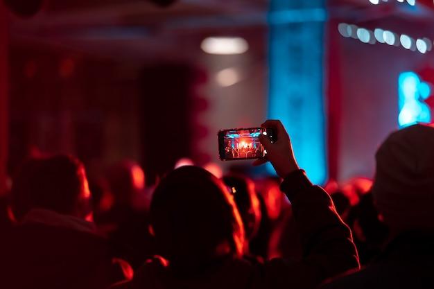 Крупным планом записи видео с помощью смартфона во время концерта. тонированное изображение Бесплатные Фотографии