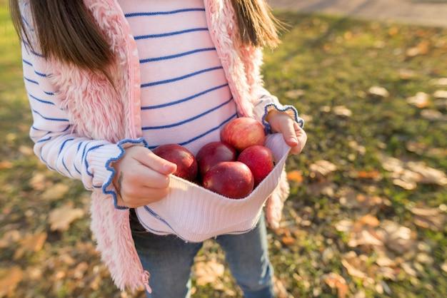 女の子の手に赤いリンゴのクローズアップ Premium写真