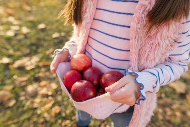 女の子の手の中の赤いリンゴのクローズアップ Premium写真