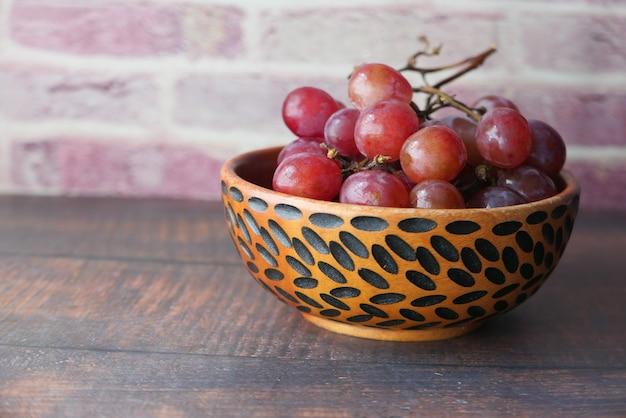 Крупным планом красного винограда в миске на столе Premium Фотографии