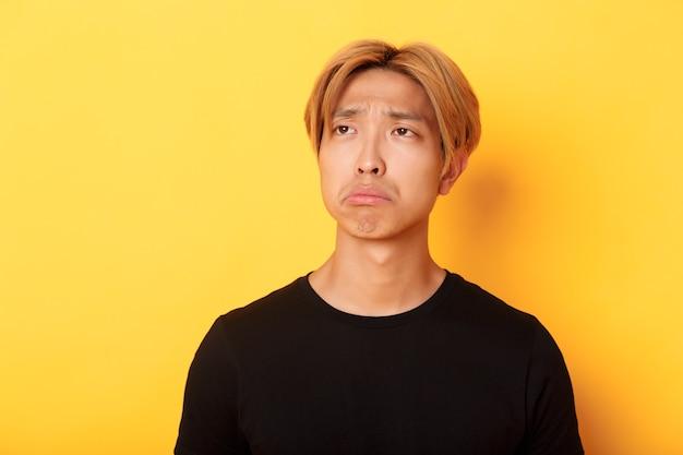 Крупный план грустного и разочарованного красивого азиатского парня, надутого и расстроенного, смотрящего в левый верхний угол с сожалением или ревностью, стоящего у желтой стены Бесплатные Фотографии