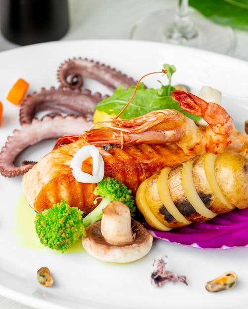 Крупным планом морепродуктов с жареным лососем осьминога, креветок и мидий Бесплатные Фотографии