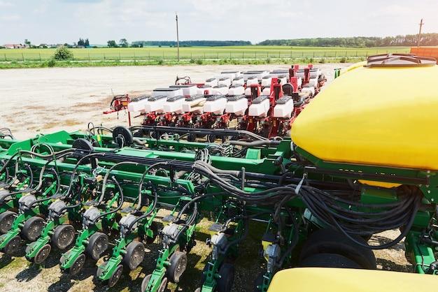 Закройте сеялку, прикрепленную к трактору в поле. Бесплатные Фотографии