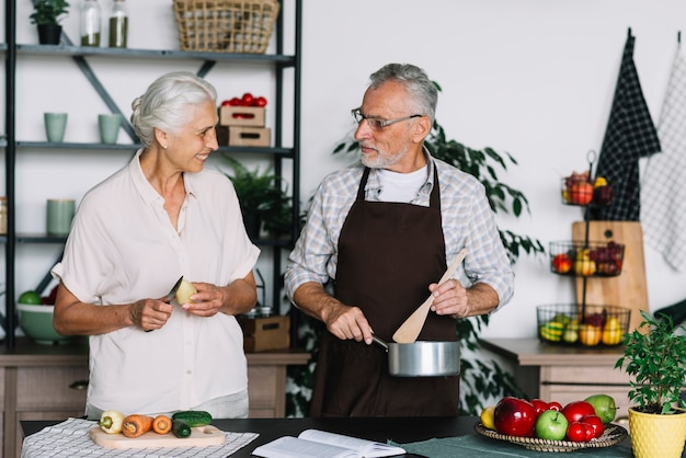 Крупным планом старших пара приготовления пищи на кухне, глядя друг на друга Бесплатные Фотографии
