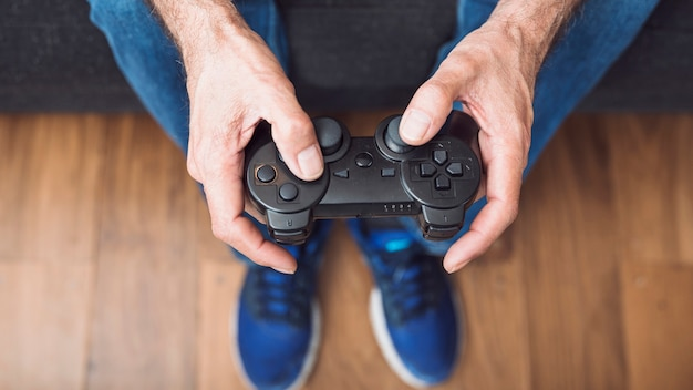 Close-up of senior man's hand holding video game console Free Photo