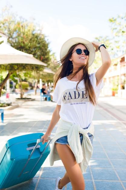 彼女の後ろに青いスーツケースのある公園を歩いて日焼けしたスリムな若い女の子のクローズアップ。彼女はデニムのショートパンツ、白いtシャツ、麦わら帽子、濃いサングラスを着ています。彼女は笑顔で片手で帽子を握る 無料写真