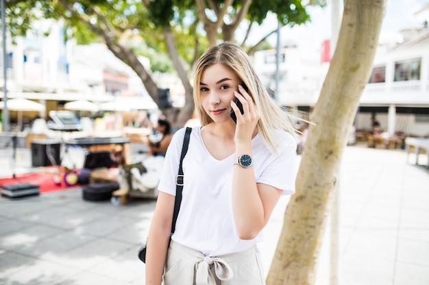 Крупным планом улыбается привлекательная девушка разговаривает по телефону, стоя на улице на улице города Бесплатные Фотографии
