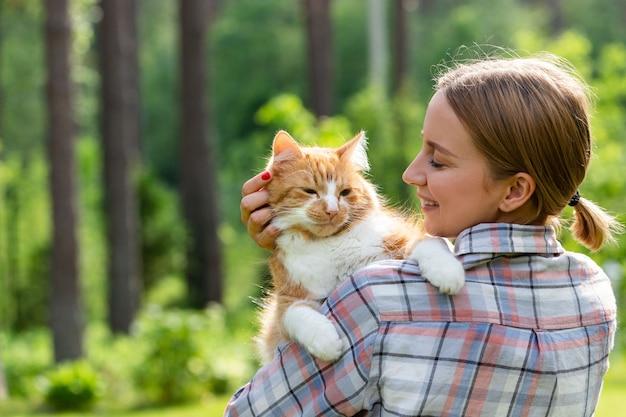 晴れた日の屋外で、優しさと抱きしめ、国産の生姜猫を愛し、頭をなでるチェックシャツを着た笑顔の女性のクローズアップ。 Premium写真