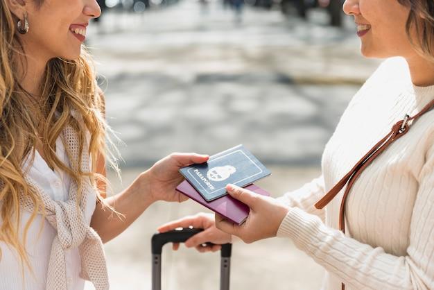 屋外でお互いに自分のパスポートを見せて笑顔の若い女性のクローズアップ 無料写真