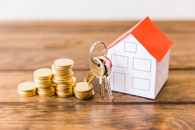 Close-up of stacked coins, house and key on wooden desk Free Photo