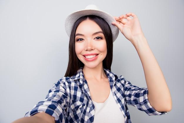 Студент, делающий автопортрет, трогающий ее кепку крупным планом Premium Фотографии