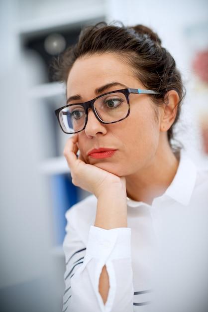 ノートパソコンの前のオフィスの机に座って退屈スタイリッシュなプロフェッショナルなビジネス女性のクローズアップ。 Premium写真