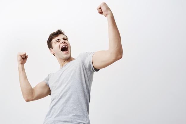 Крупный план успешного молодого кавказского мужского спортсмена, кричащего да и поднимающего сжатые кулаки в воздухе, чувствуя взволнованный. люди, успех, триумф, победа, победа и праздник. Бесплатные Фотографии