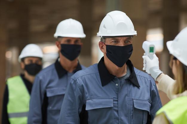 Крупный план руководителя измерения температуры рабочих с помощью бесконтактного термометра на строительной площадке, безопасность от коронавируса Premium Фотографии