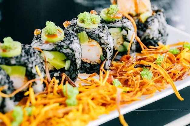 天ぷらとアボカドの黒巻きご飯で覆われた巻き寿司のクローズアップ 無料写真