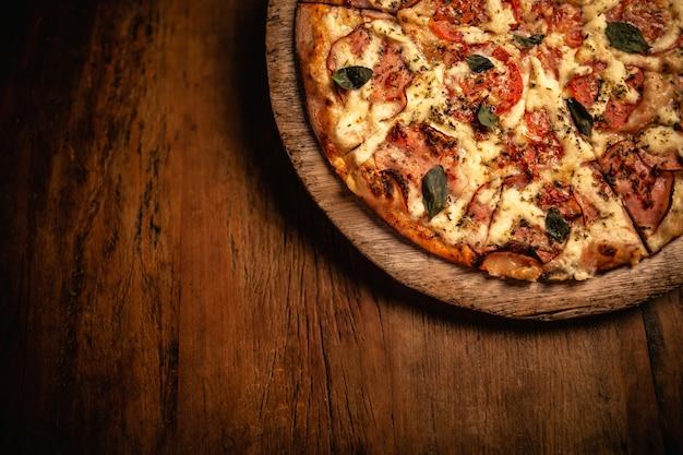 木製のまな板でおいしいピザのクローズアップ Premium写真