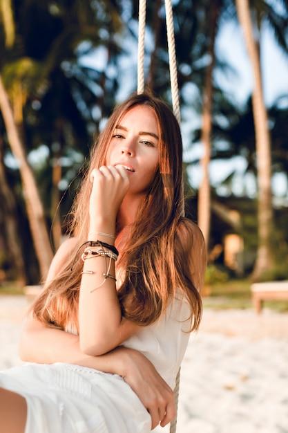 Крупный план нежной девушки, сидящей на качелях в белом платье. у нее длинные темные волосы. на руке у нее браслеты. качели на пляже с зелеными пальмами Бесплатные Фотографии