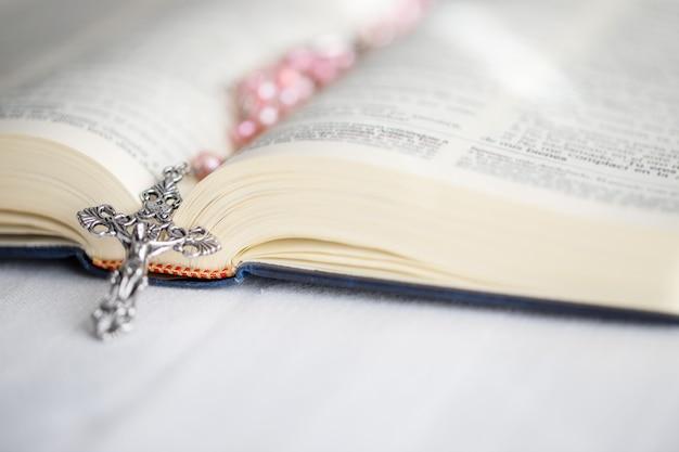 開いた聖書の十字架のクローズアップ。信仰、精神性、キリスト教の宗教概念。 Premium写真