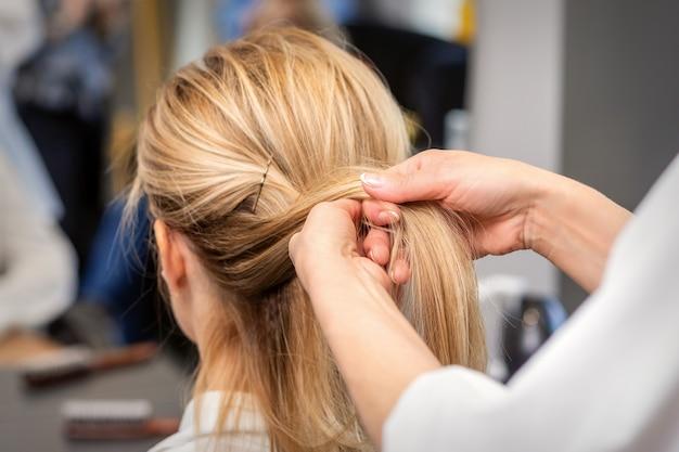 미용실에서 고객의 머리카락을 땋는 미용사의 손을 닫습니다. 프리미엄 사진