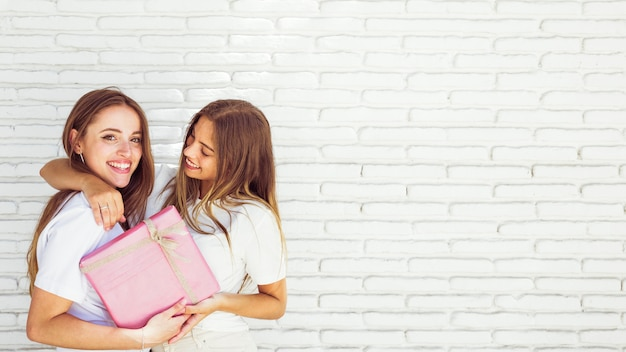 Close Up Of Two Happy Female Friends With Birthday Gift Free Photo