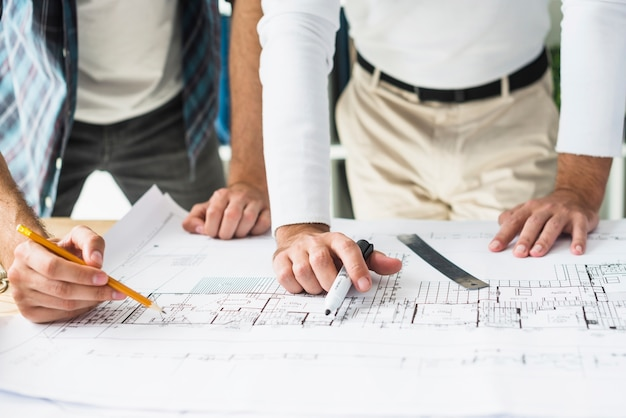 Close-up of two male architect's hand over blueprint Free Photo