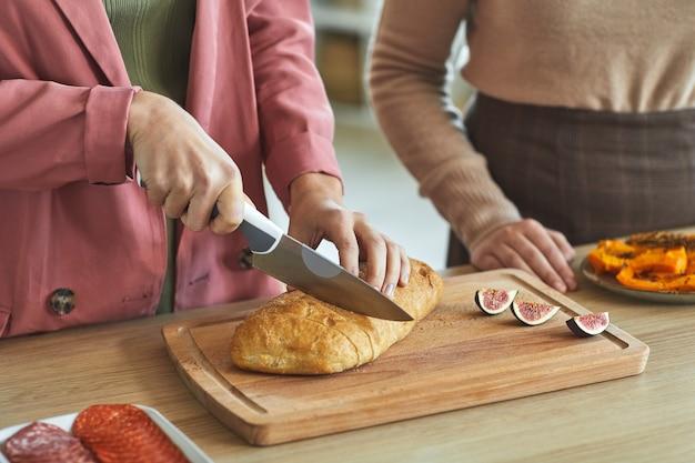 ディナーパーティーのために料理をしながら焼きたてのパンを切る2人の認識できない女性のクローズアップ、 Premium写真