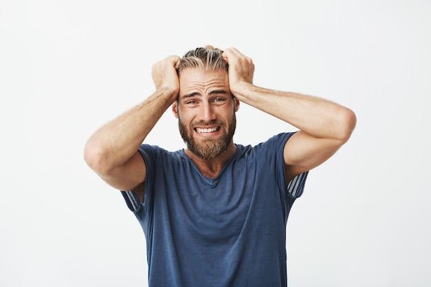 ひげの手で髪を保持している不幸なハンサムな男のクローズアップ 無料写真