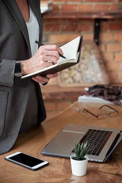 机に立って日記にアイデアを書き留めているジャケットの認識できない実業家のクローズアップ Premium写真