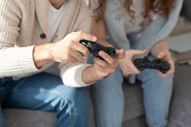 ビデオゲームを楽しみながらジョイスティックを使用してカジュアルな服装で認識できない友人のクローズアップ Premium写真