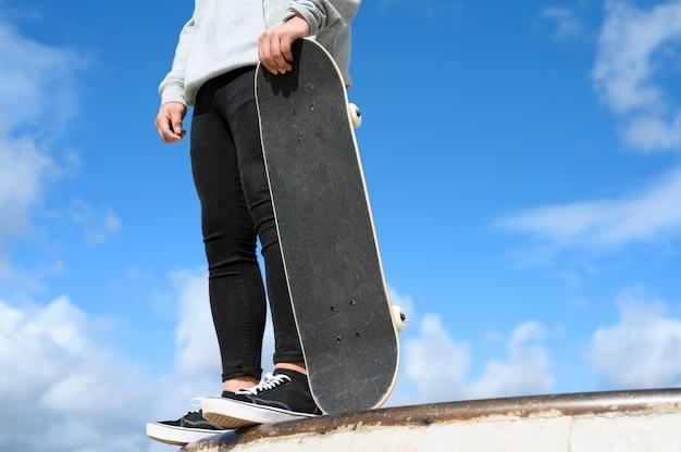 青い空を背景に公園でスケートボードを保持している認識できない若い男のクローズアップ。 Premium写真
