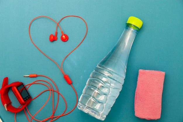 水のボトル、時計、赤いイヤホン、緑の背景にタオルクロスのクローズアップ。フィットネスの背景の概念。 Premium写真