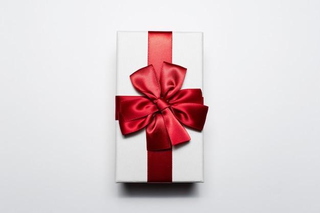 붉은 나비, 흰색 배경에 고립 된 흰색 선물 상자의 근접. 프리미엄 사진