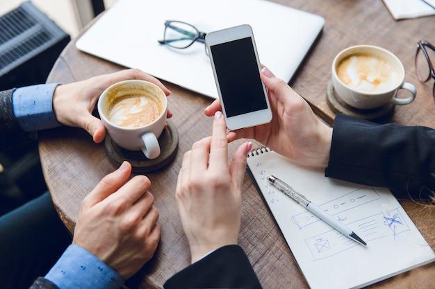 女性の手の中の白いスマートフォンのクローズアップ。コーヒーを飲みながらコーヒーテーブルに座っている2人の同僚 無料写真