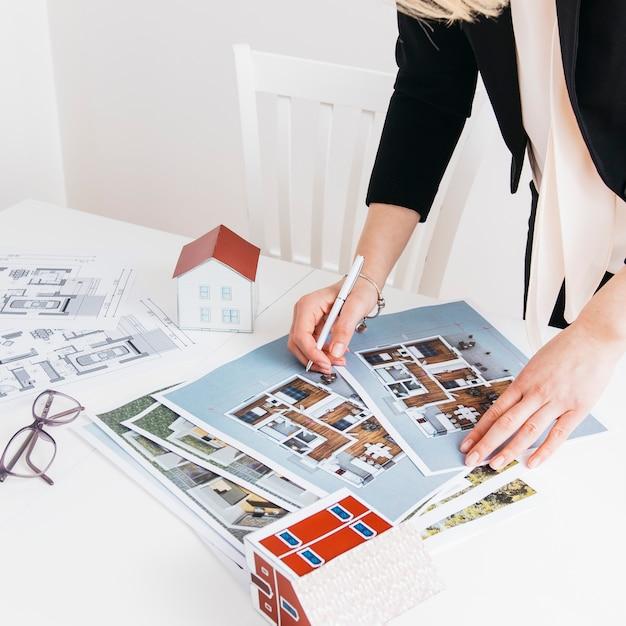 オフィスでの青写真に取り組んでいるペンを持つ女性の手のクローズアップ Premium写真